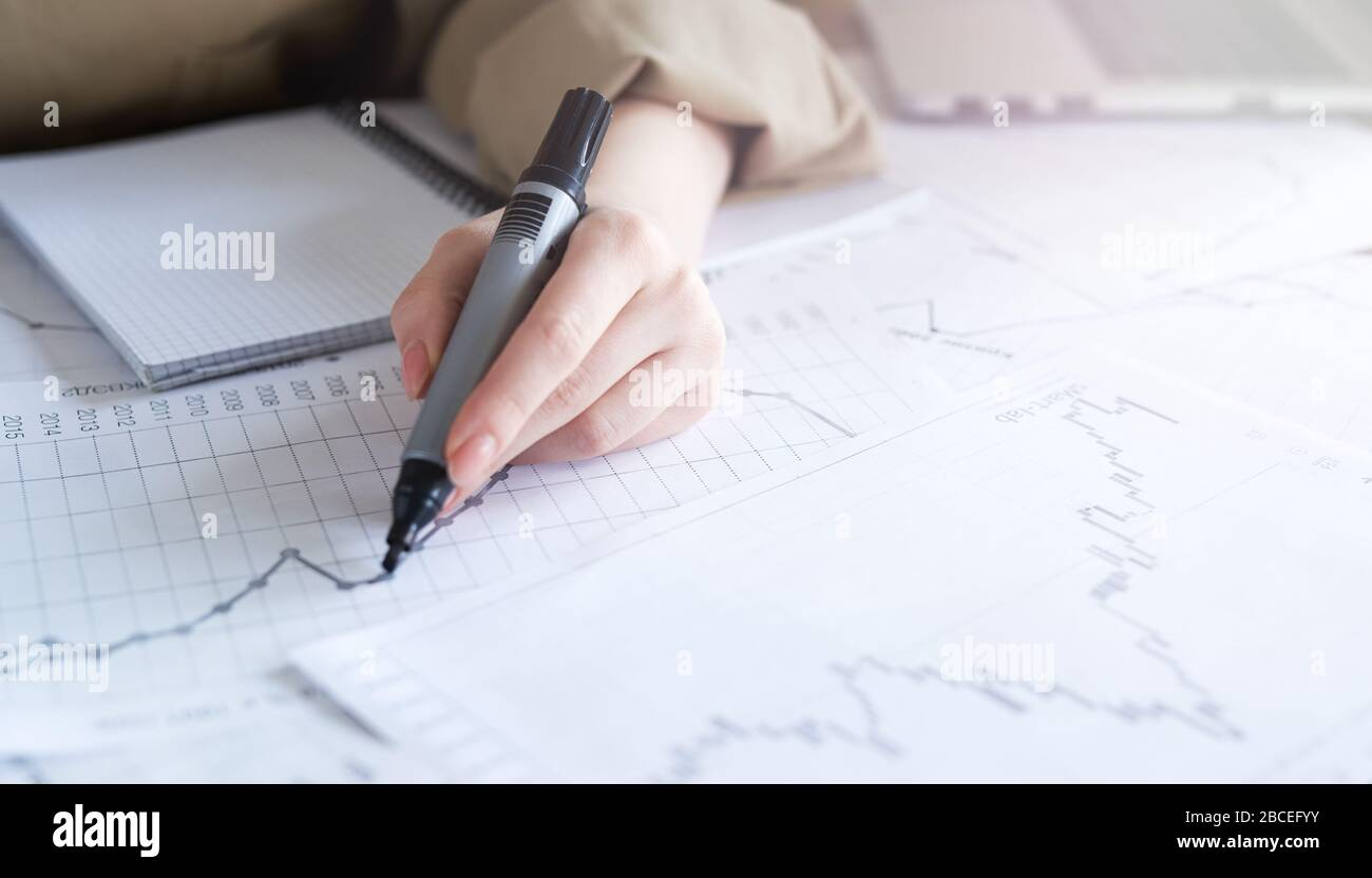 Close up woman hand working of Business graphics, analysis. Startup Stock Photo