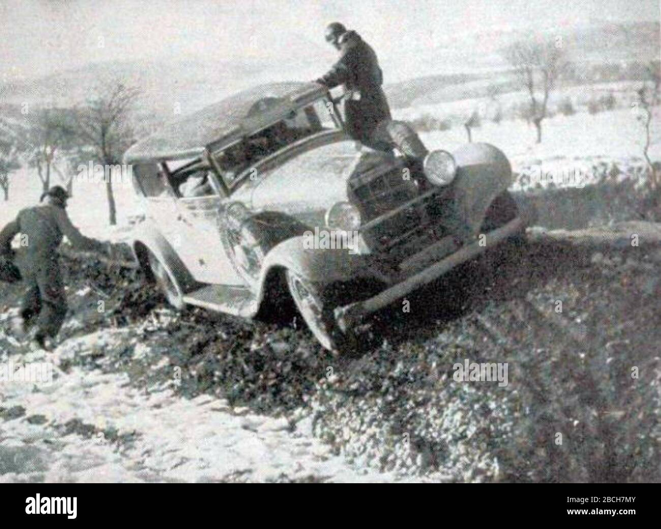 """""""Français: Rallye Monte Carlo 1934, la Hotchkiss de Gas et Trévoux.English: This seems like entry #4 in the 1934 Rallye Monte Carlo, which should have been a Hotchiss AM 80 S 3,485 ccm[1] but the car in this picture does NOT look quite similar (this one has a bumper, extra spare wheel, and not rounded radiator), so perhaps from a different year, or maybe it is not a 4 on the plaque mounted on the roof.; 4 November 2017; Omnia: revue pratique de locomotion, n°173, octobre 1934; Omnia; """" Stock Photo"""