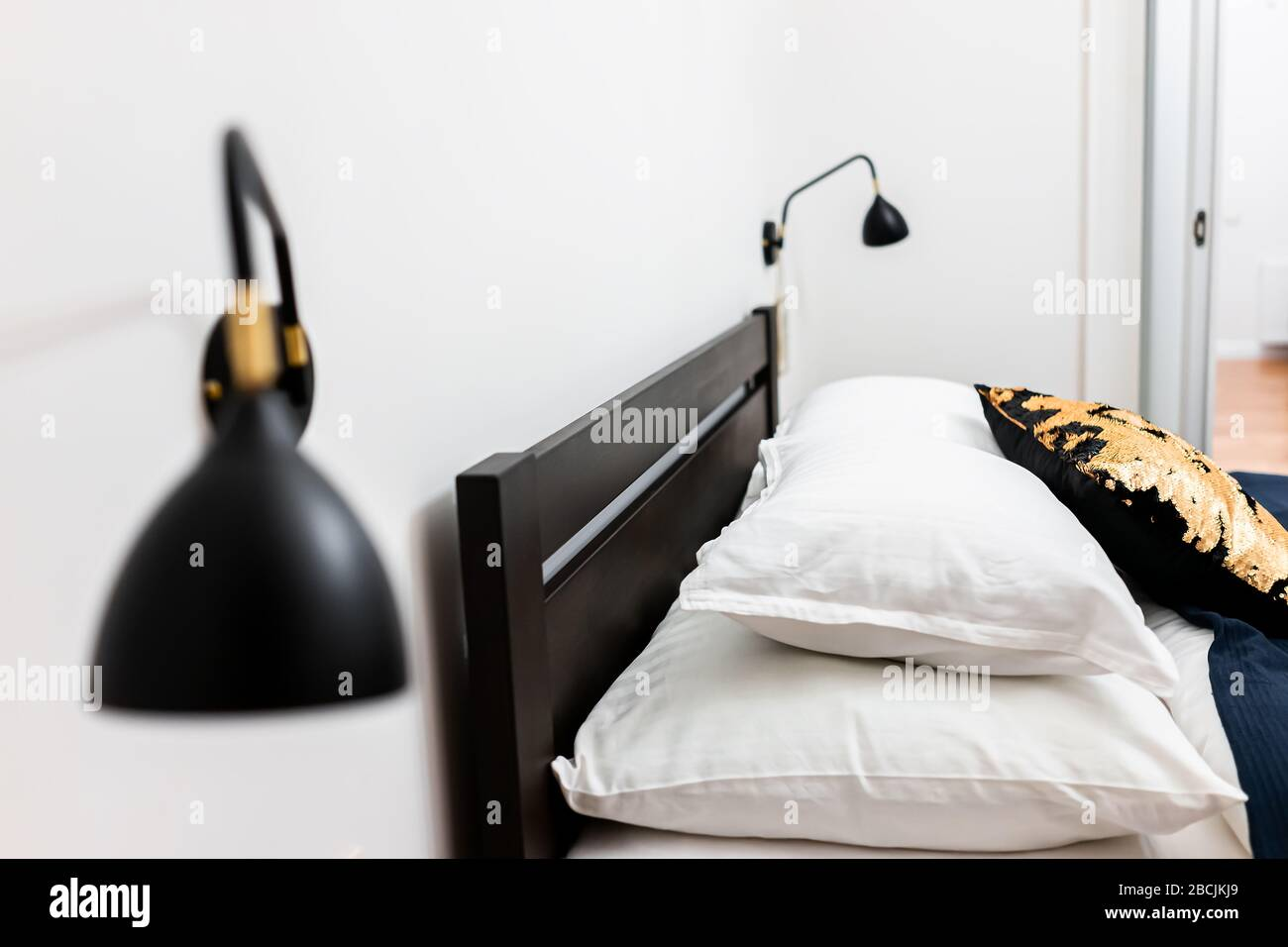 New Clean Queen Bed With Wall Mounted Lights Lamps Decorative Pillows In Bedroom Home House Or Hotel Apartment Side View Closeup Stock Photo Alamy