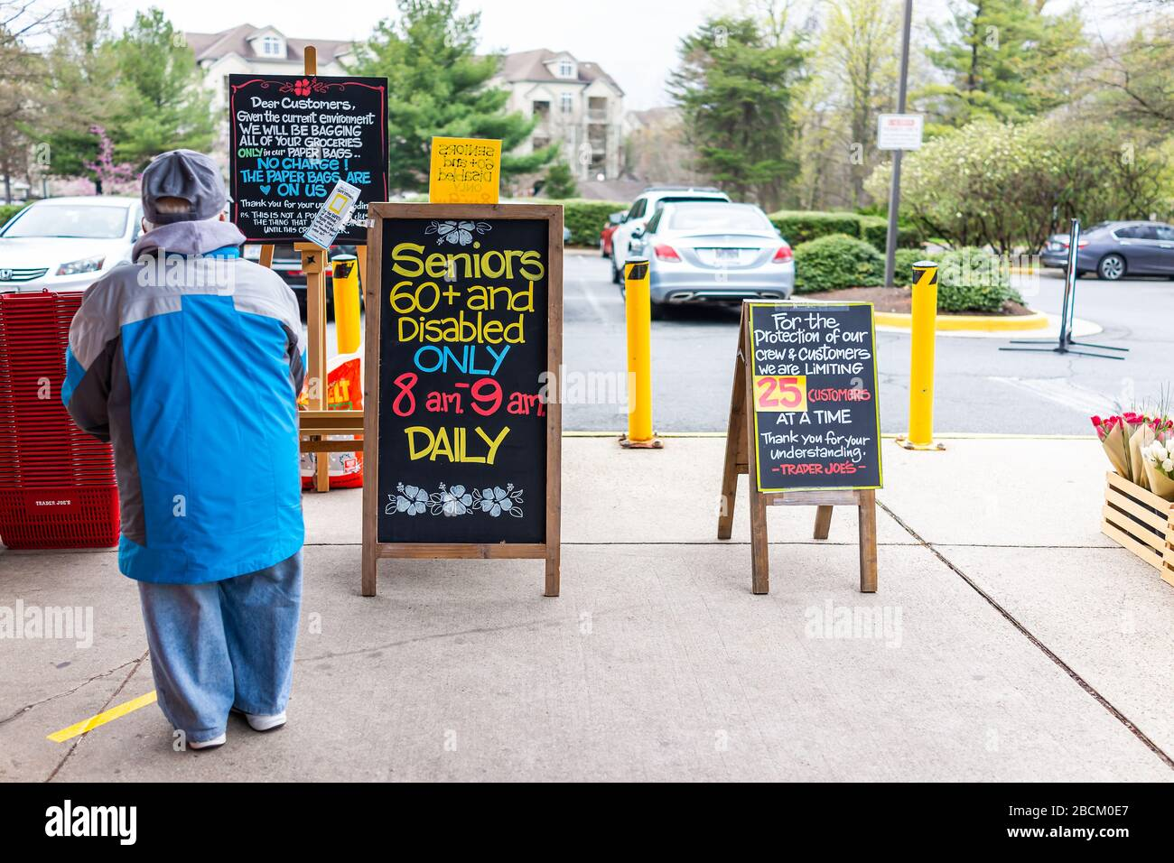 Reston, USA - April 1, 2020: Trader Joe's grocery store sign for senior disabled customers special hours, customer limit and grocery bagging paper bag Stock Photo