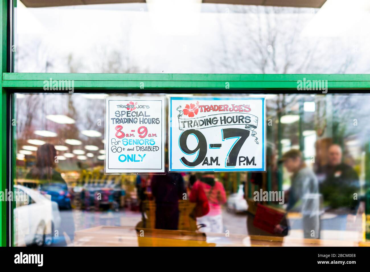 Reston, USA - April 1, 2020: Trader Joe's grocery store window sign for senior customers with special morning and regular open hours for old people du Stock Photo