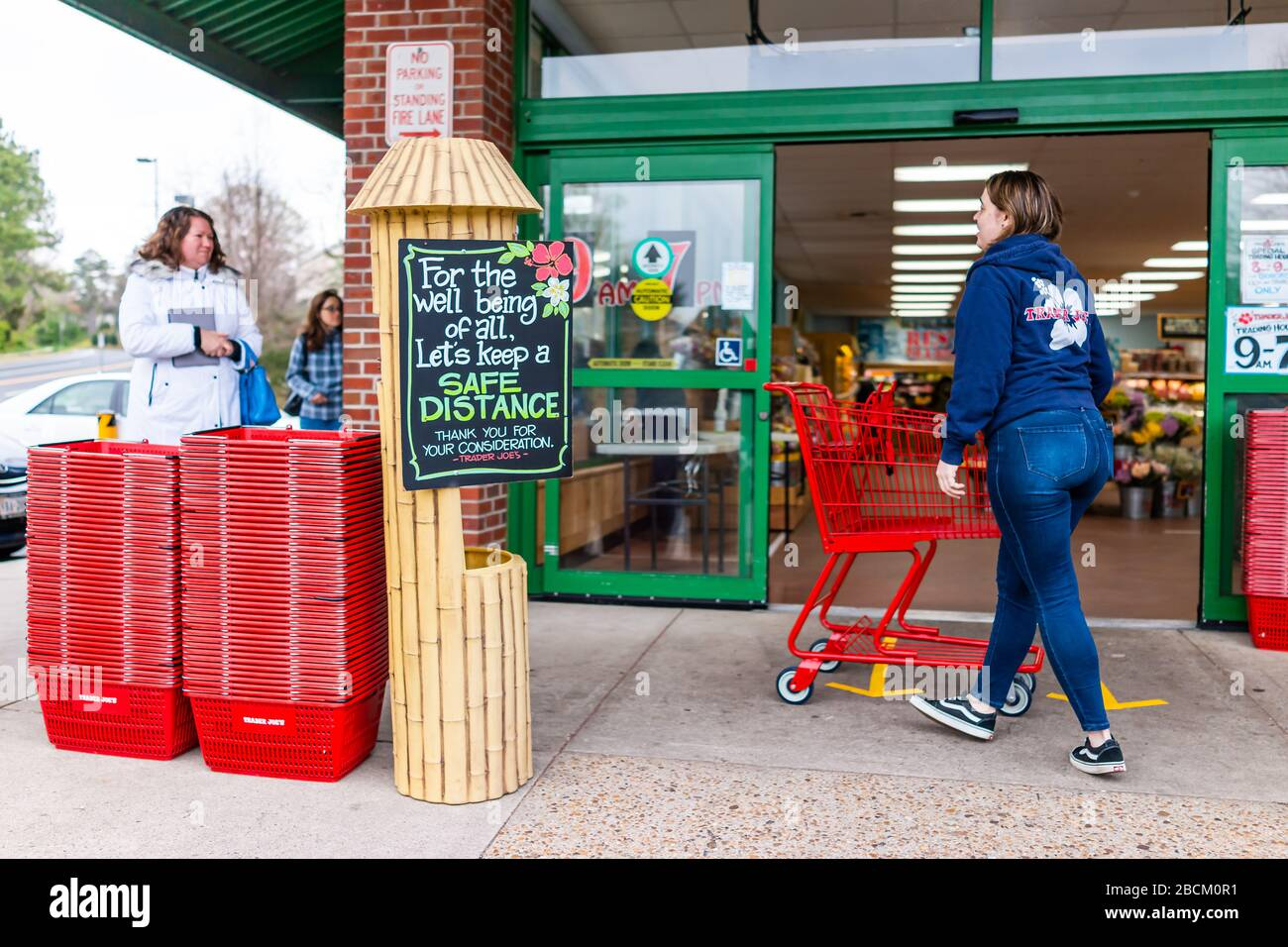Reston, USA - April 1, 2020: Trader Joe's grocery store sign for social distance customer distancing by shop entrance with people in line, employee wo Stock Photo