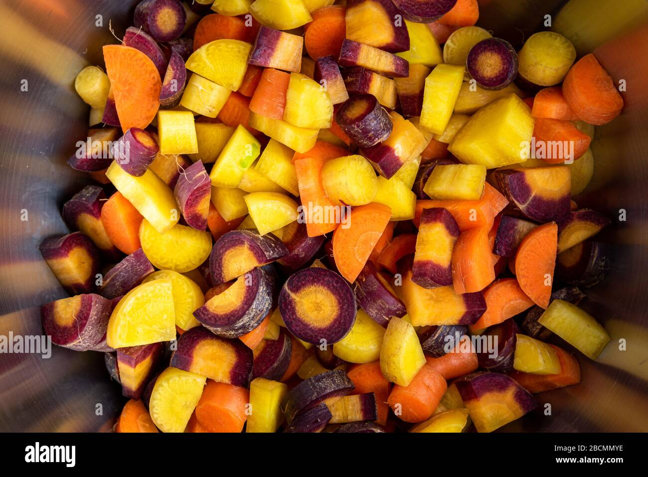 Diced rainbow carrots in a stainless-steel bowl, close-up Stock Photo