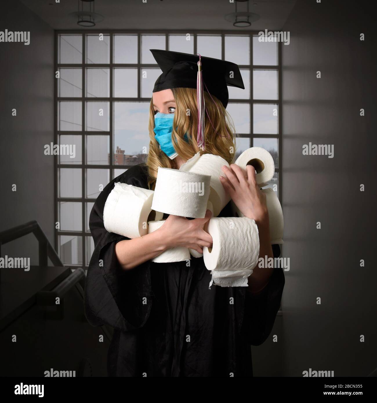 A senior graduate from the class of 2020 is graduating inside holding toilet paper as a humorous portrait concept. Stock Photo