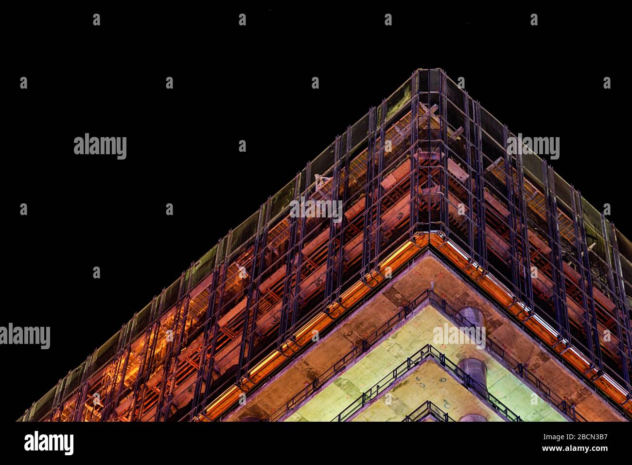 Looking up at a high rise construction site lit up at night in Perth during the boom Stock Photo