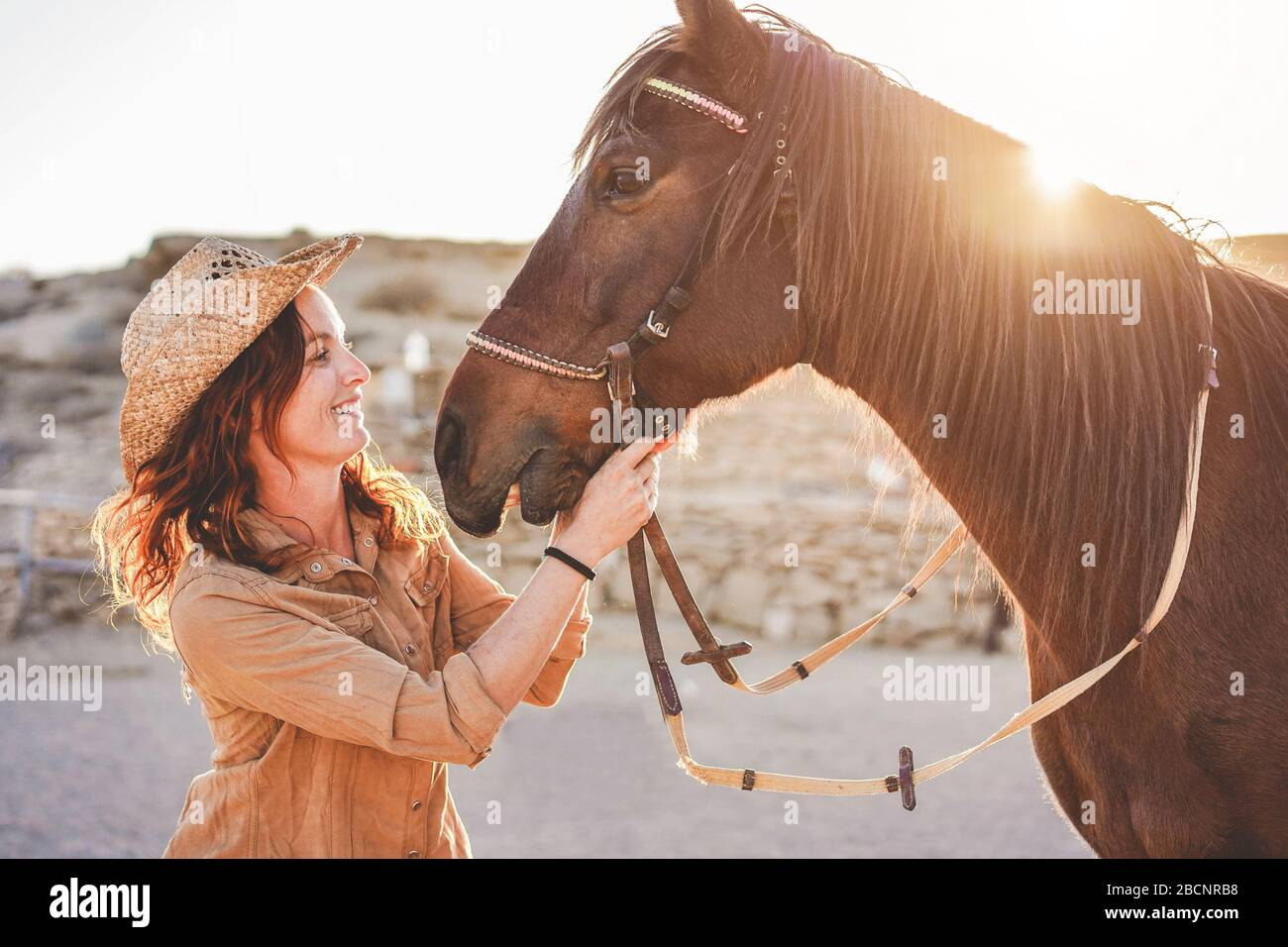 Young farmer woman playing with her bitless horse in a sunny day inside corral ranch - Concept about love between people and animals - Focus on girl f Stock Photo