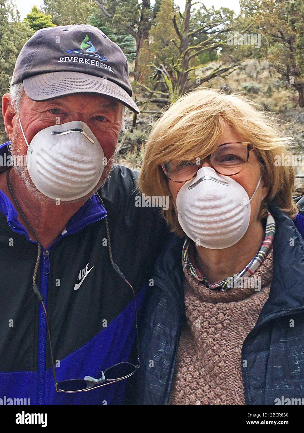A middle-aged couple wearing dust masks as they leave their home in central Oregon for a grocerly shopping trip into the city of Bend, Oregon. Stock Photo