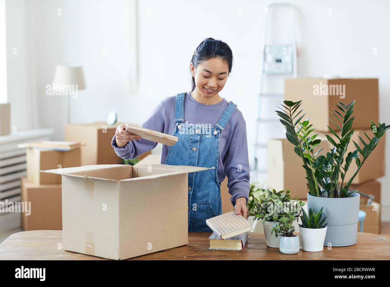 Waist up portrait of young Asian woman packing or unpacking cardboard box and smiling happily while moving into new home, copy space Stock Photo