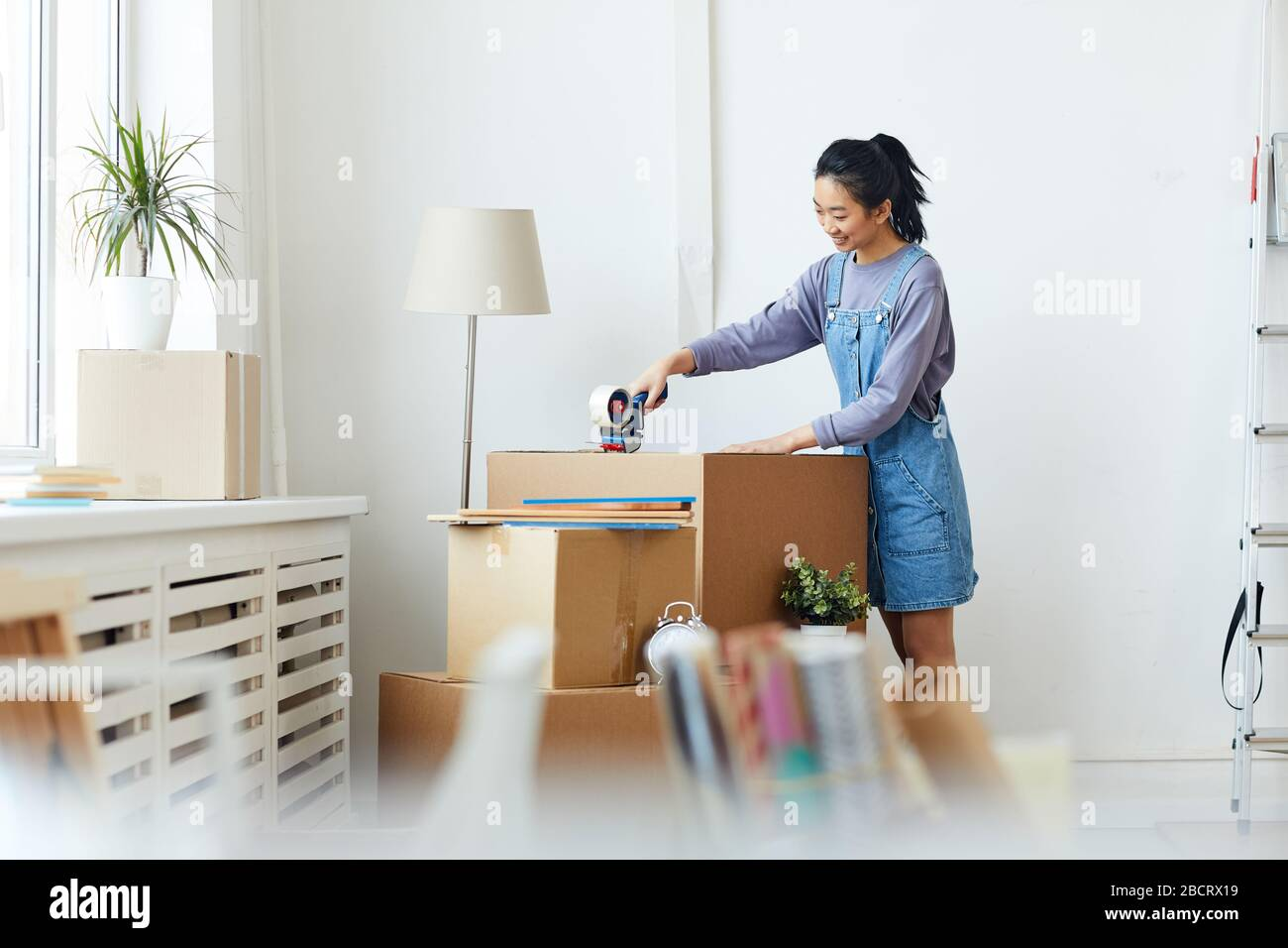 Side view portrait of young Asian woman packing cardboard boxes and smiling happily while moving to new home or apartment, copy space Stock Photo