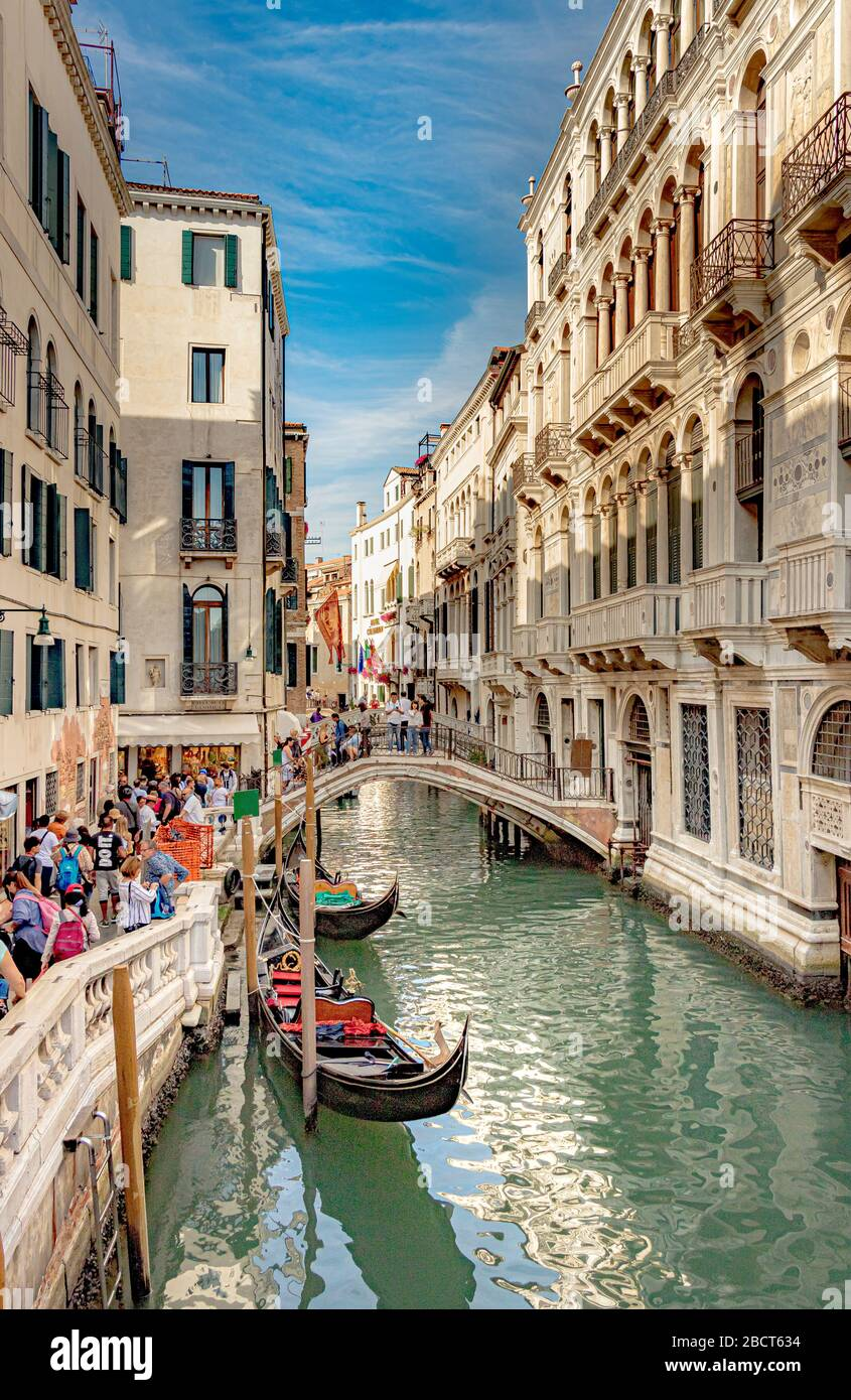 People crossing a canal bridge with two gondolas moored at the canal side along the rio del Palazzo canal near the Doges Palace ,Venice Stock Photo