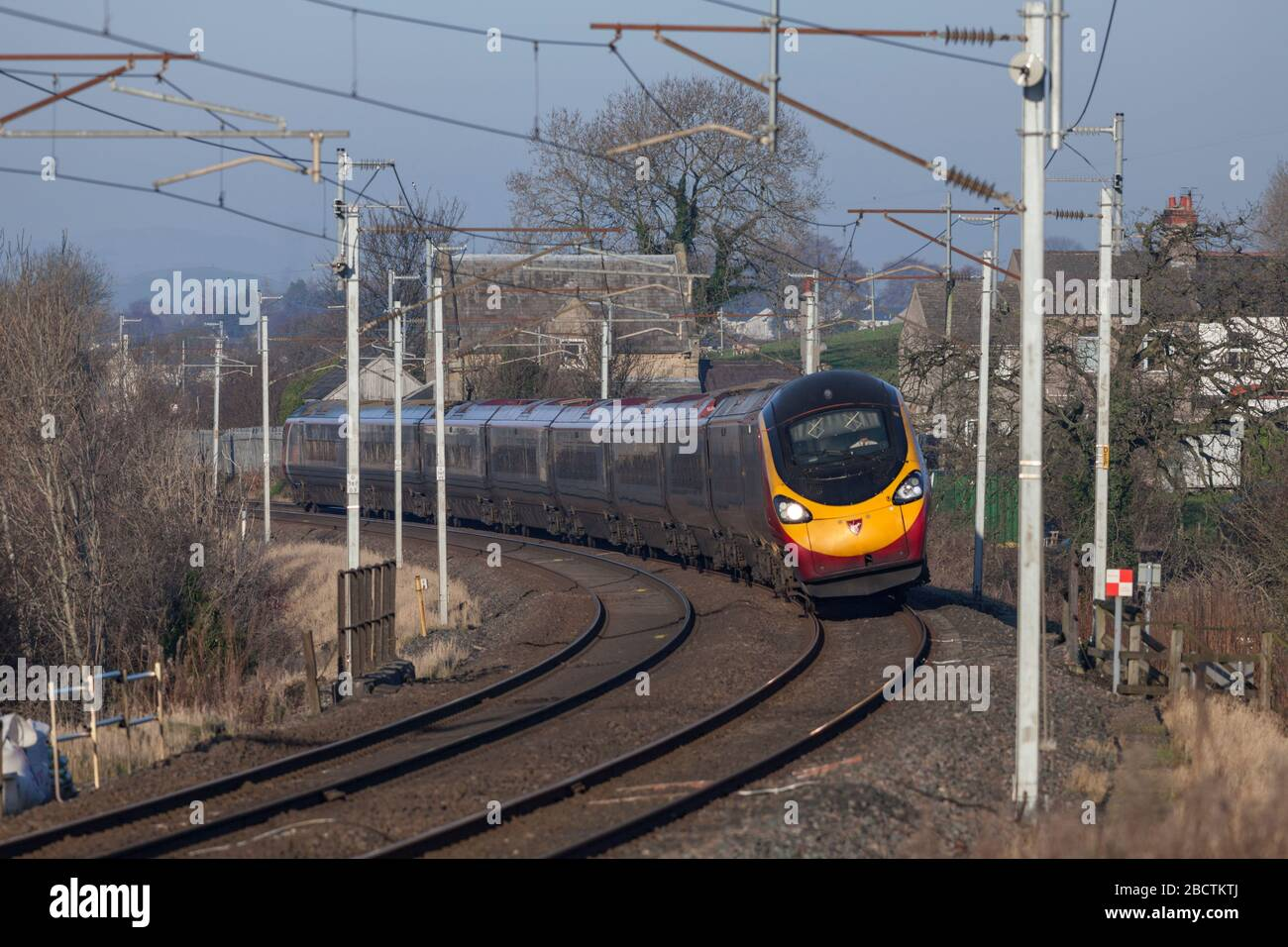 Virgin trains Alstom class 390 Pendolino tilting train tilting around a curve on the west coast mainline in Cumbria Stock Photo
