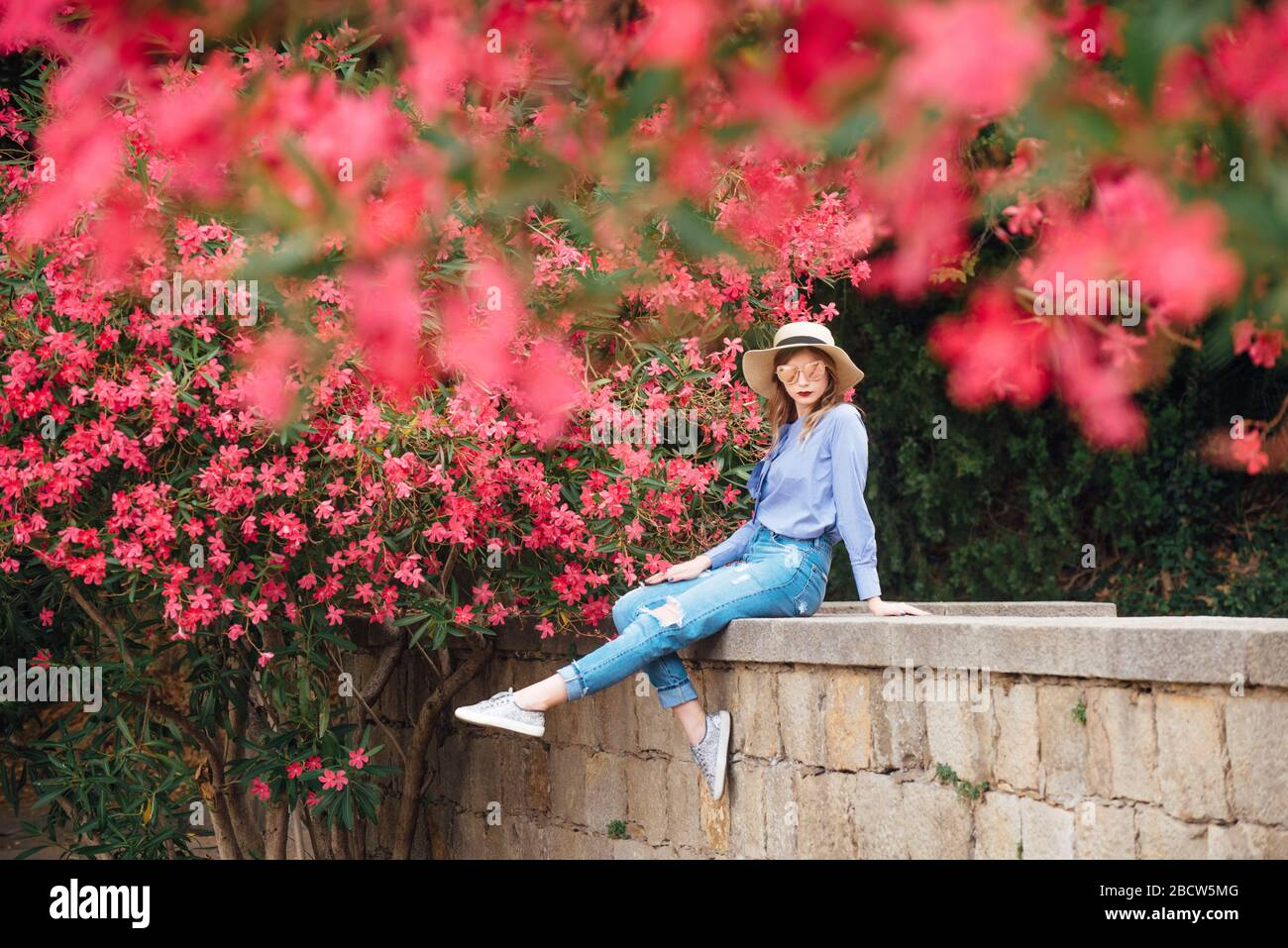 The girl next to the bushes with flowers in a hat and a stylish jacket. beautiful makeup Stock Photo