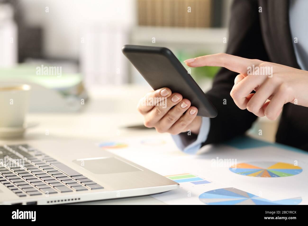 Close up of business woman hands checking smart phone on a desk at the office Stock Photo