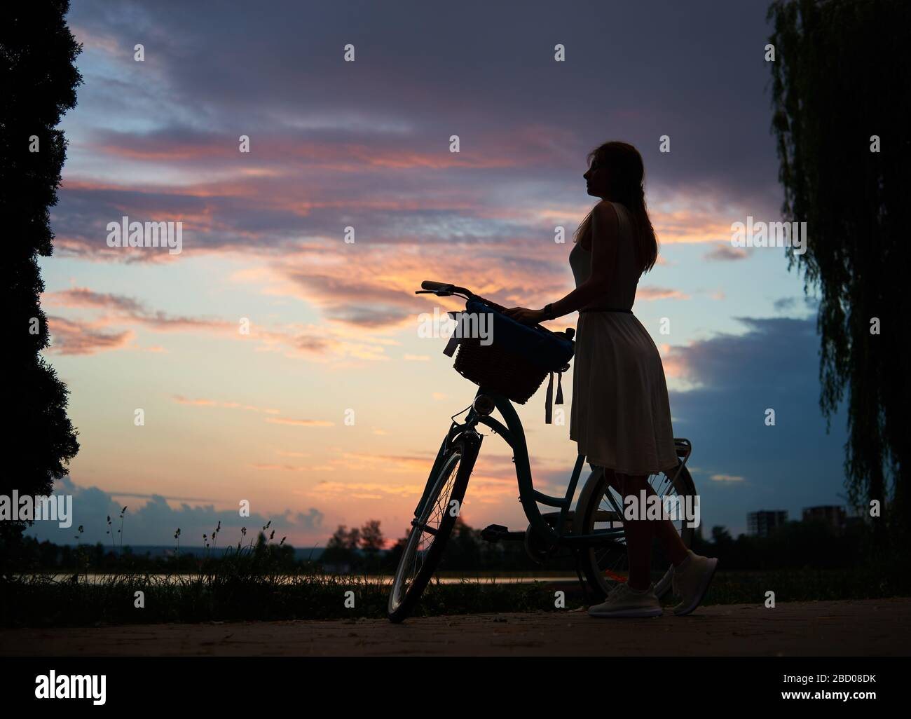 Woman in a light dress with retro bike under the sky at sunset. Enjoying a beautiful view of the evening sky with clouds colorful in summer. The concept of freedom and relaxation Stock Photo
