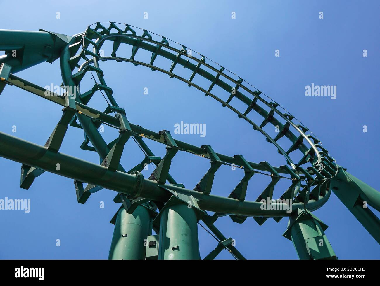 Curved Rollercoaster at a theme or amusement park empty green metal tracks and on blue sky background Stock Photo