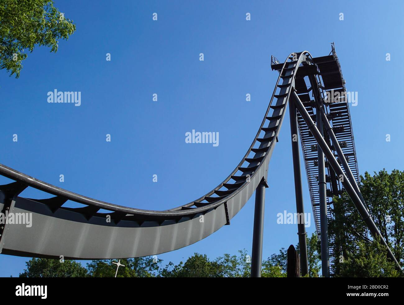 Rollercoaster track against a brilliant blue sky . Stock Photo