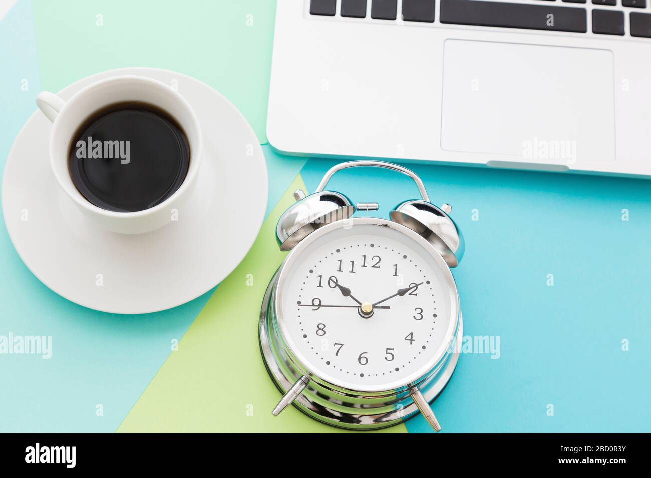 Overhead view of objects for office time concept with cup of black coffee and classic metal alarm clock, next to smartphone and open laptop, arranged Stock Photo