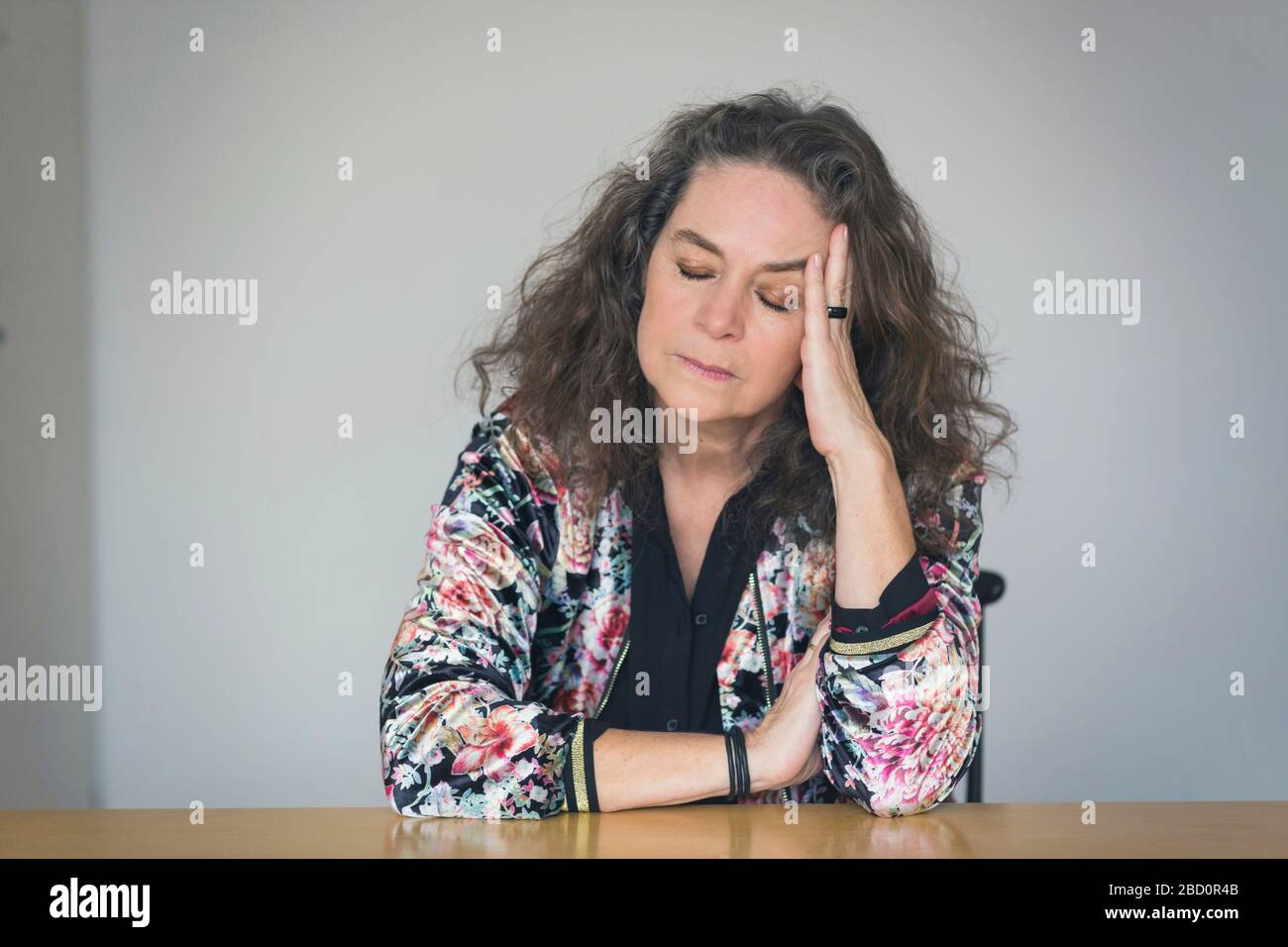 Depressed or unwell pretty middle-aged woman seated at a table indoors resting her head on her hand with closed eyes and a serious withdrawn expressio Stock Photo