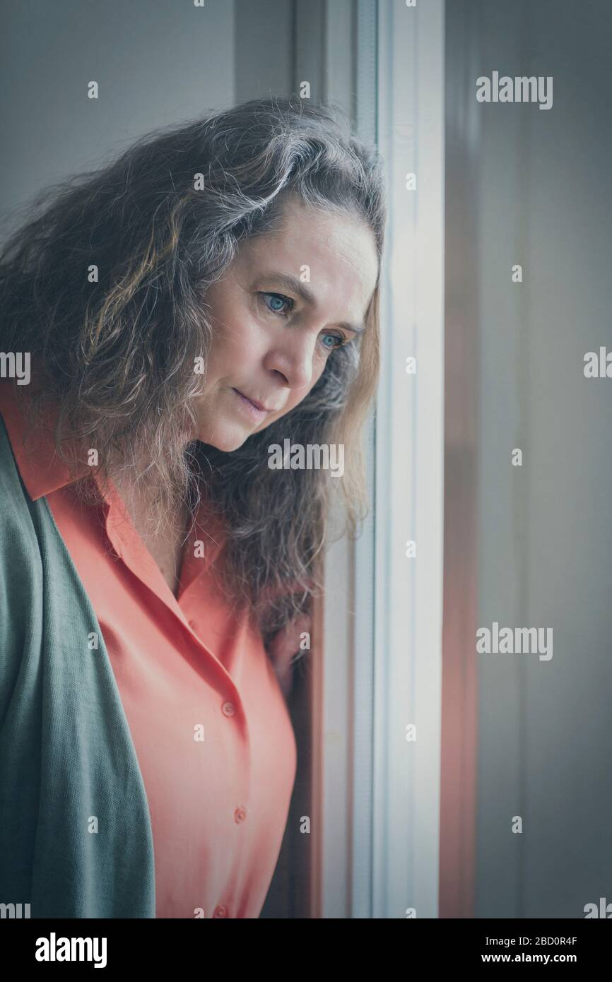 Thoughtful woman leaning her head on a window staring outside watching something intently Stock Photo