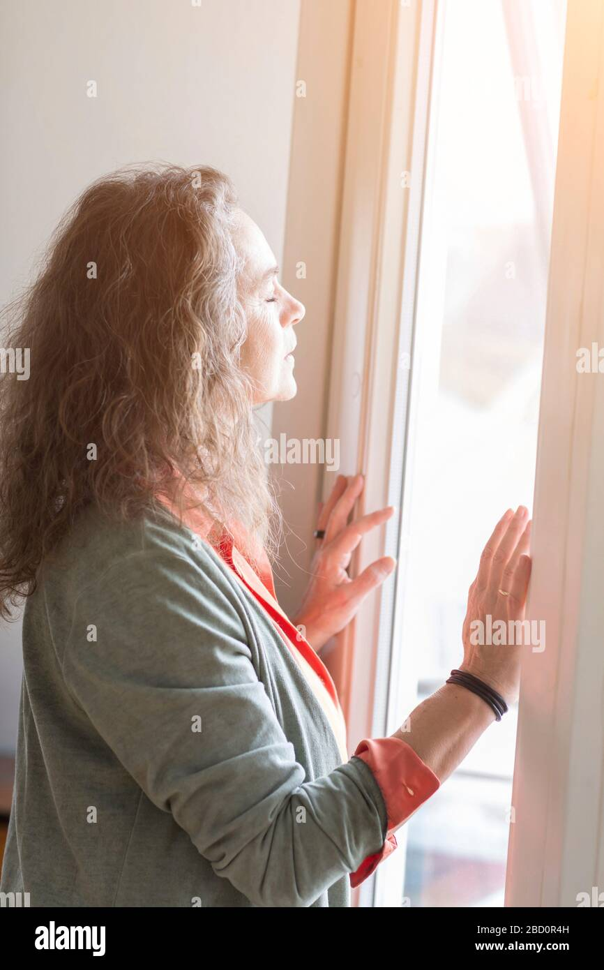 Attractive middle-aged woman enjoying the warmth of the sunlight as she stands in front of a window with closed eyes and a blissful expression Stock Photo