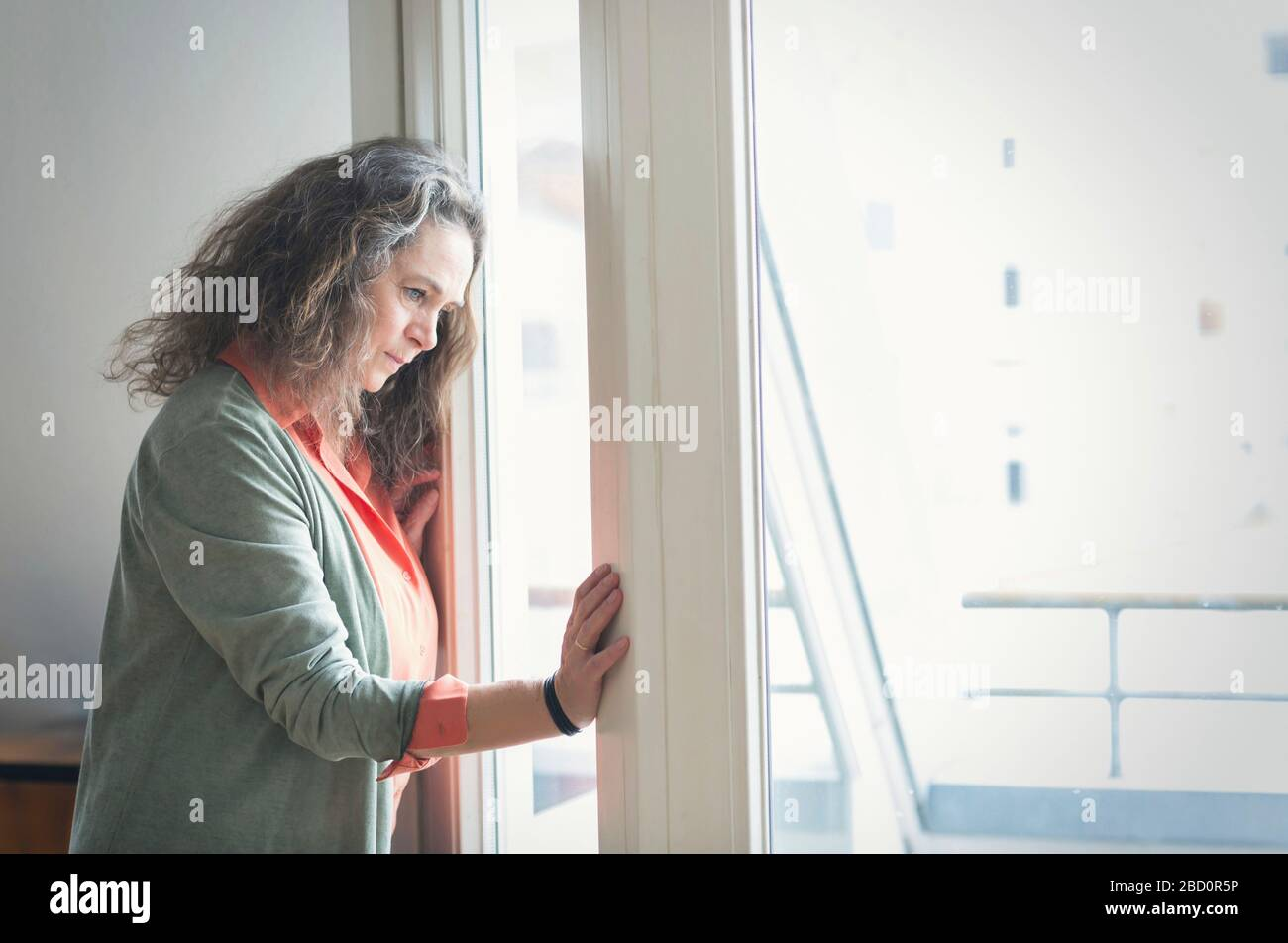 Attractive mature woman with long curly hair standing indoors looking out of a window with a thoughtful expression at something below Stock Photo