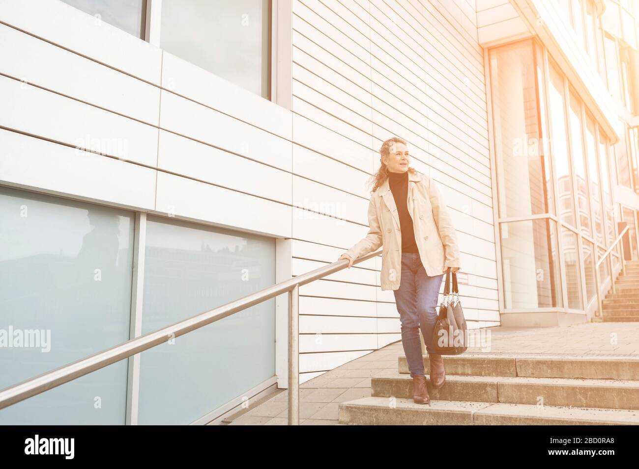 Attractive stylish mature woman descending exterior steps in town by the warm glow of the sun looking off to the side Stock Photo