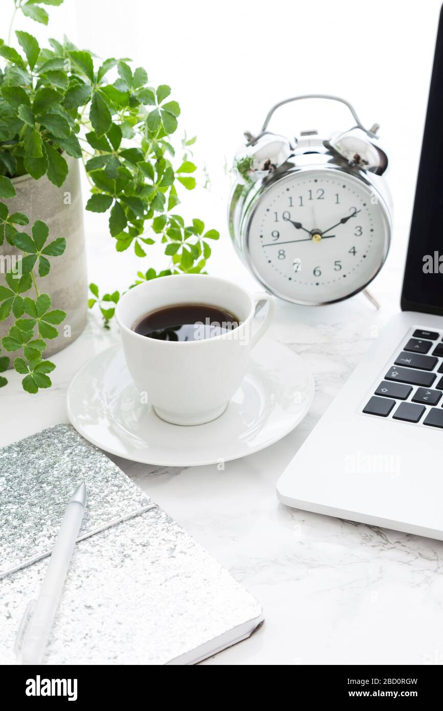 Closeup of coffee open laptop and classic alarm clock on desk in office Stock Photo