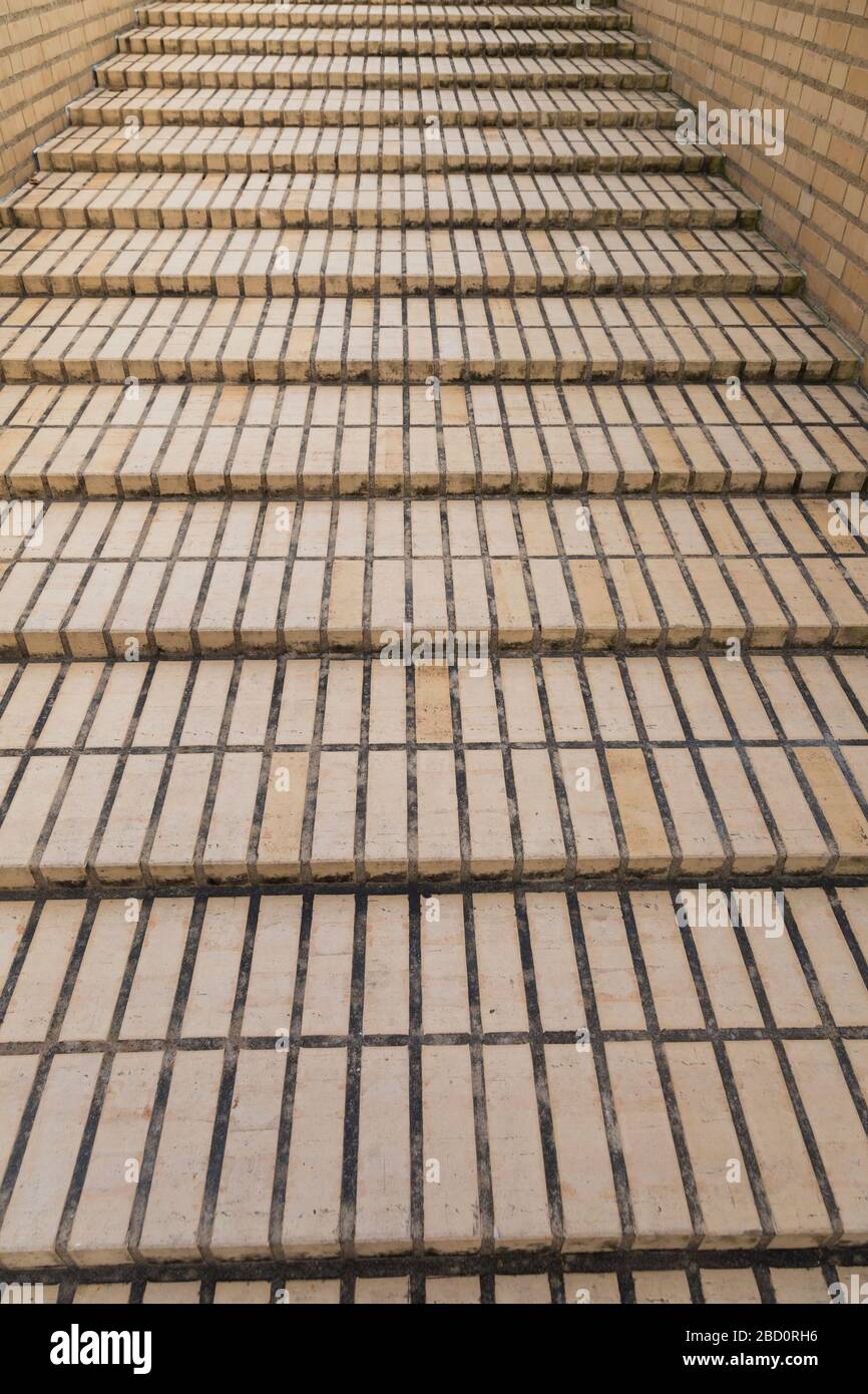 Long flight of shallow brick paved steps viewed from the bottom looking up between two matching walls Stock Photo