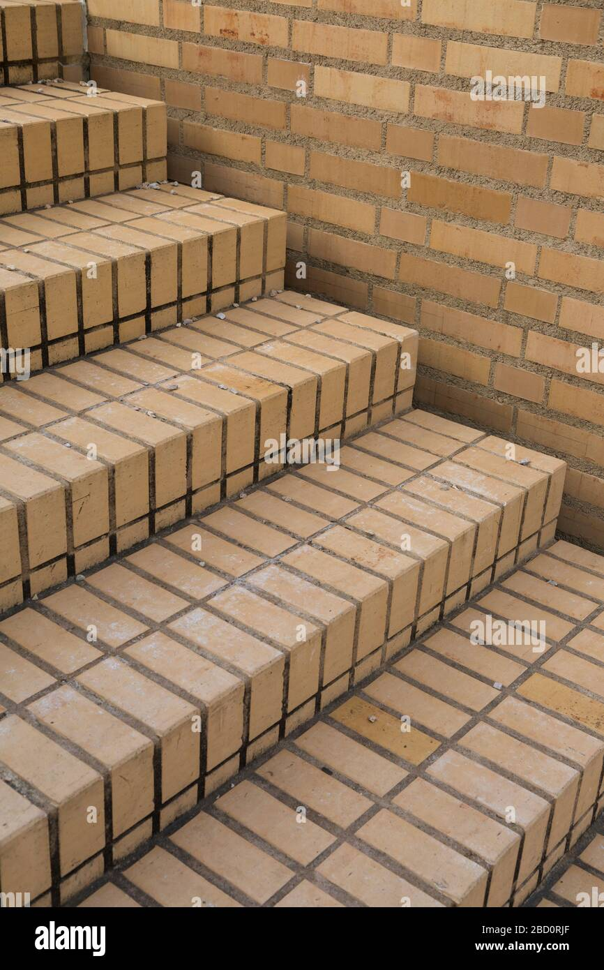 Staircase of orange clay face brick paving bordered by a wall in a close up oblique angle view for an architectural background Stock Photo