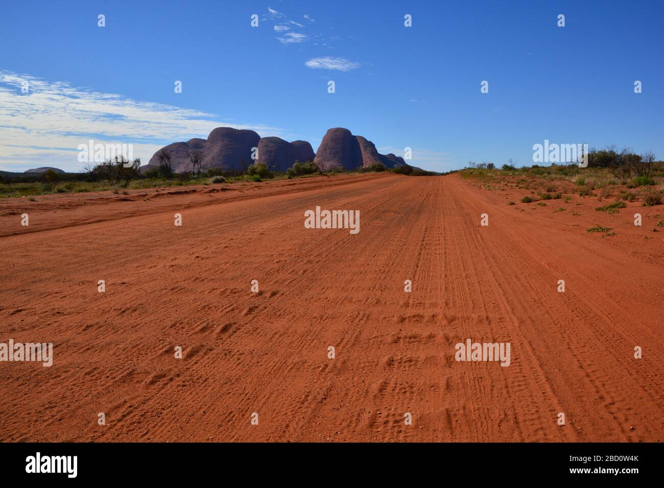 Northern Territory, Australia: low angle wide view of red dust road in the outback with the rock formation of Kata Tjuta or Olgas in the bac Stock Photo