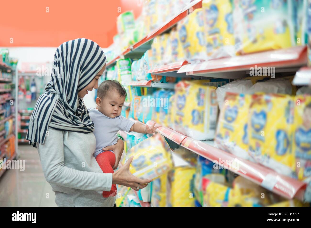 muslim asian mother buying baby product while carrying her daughter Stock Photo