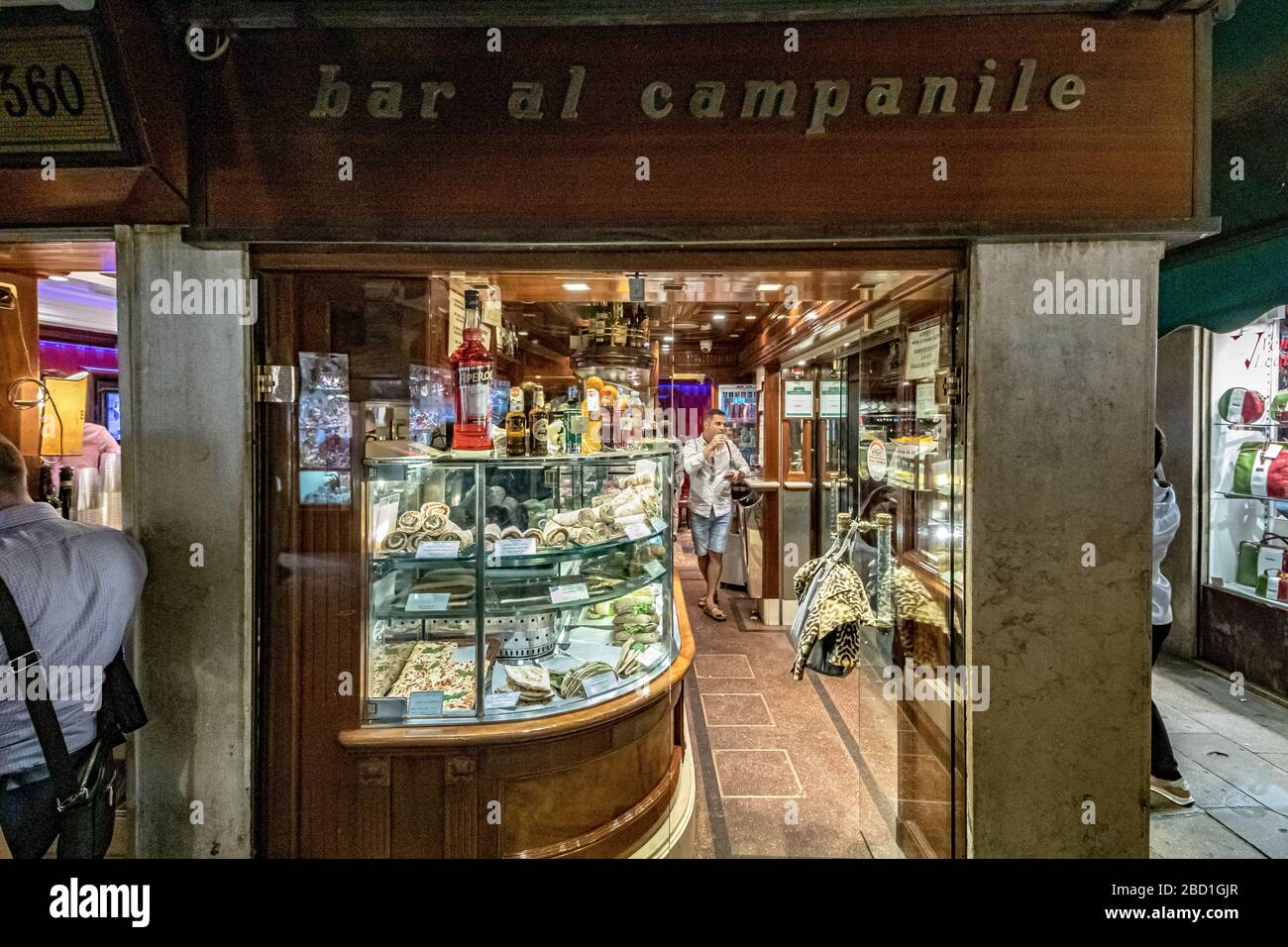 A man enjoys an glass of wine and some cicchetti standing inside Bar Al Campanile on Calle Larga S. Marco , Venice,Italy Stock Photo