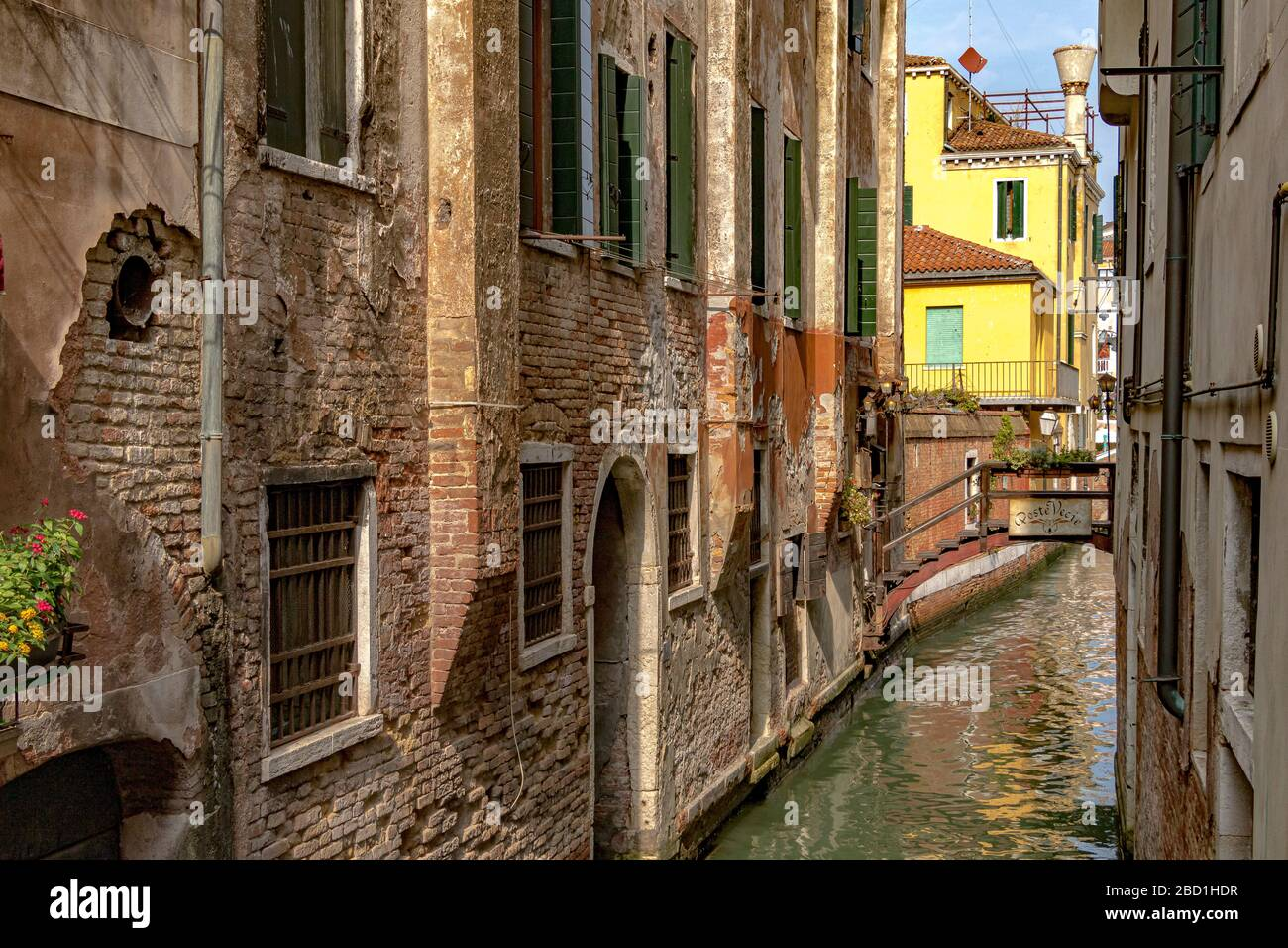 A narrow canal with a small wooden bridge leading to Poste Vecie an Italian restaurant near Rialto fish market in Venice,Italy Stock Photo