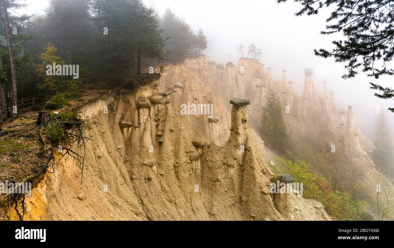 Earth Pyramids and woods in the autumn mist, Perca (Percha), province of Bolzano, South Tyrol, Italy, Europe Stock Photo