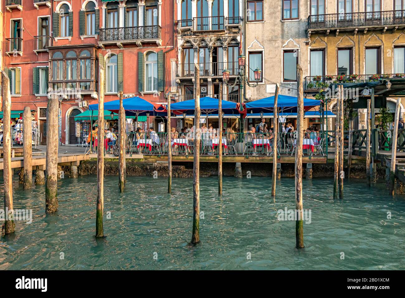 Diners eating outdoors at an Italian restaurant in front of wooden mooring poles near Rialto on The Grand Canal ,Venice ,Italy Stock Photo