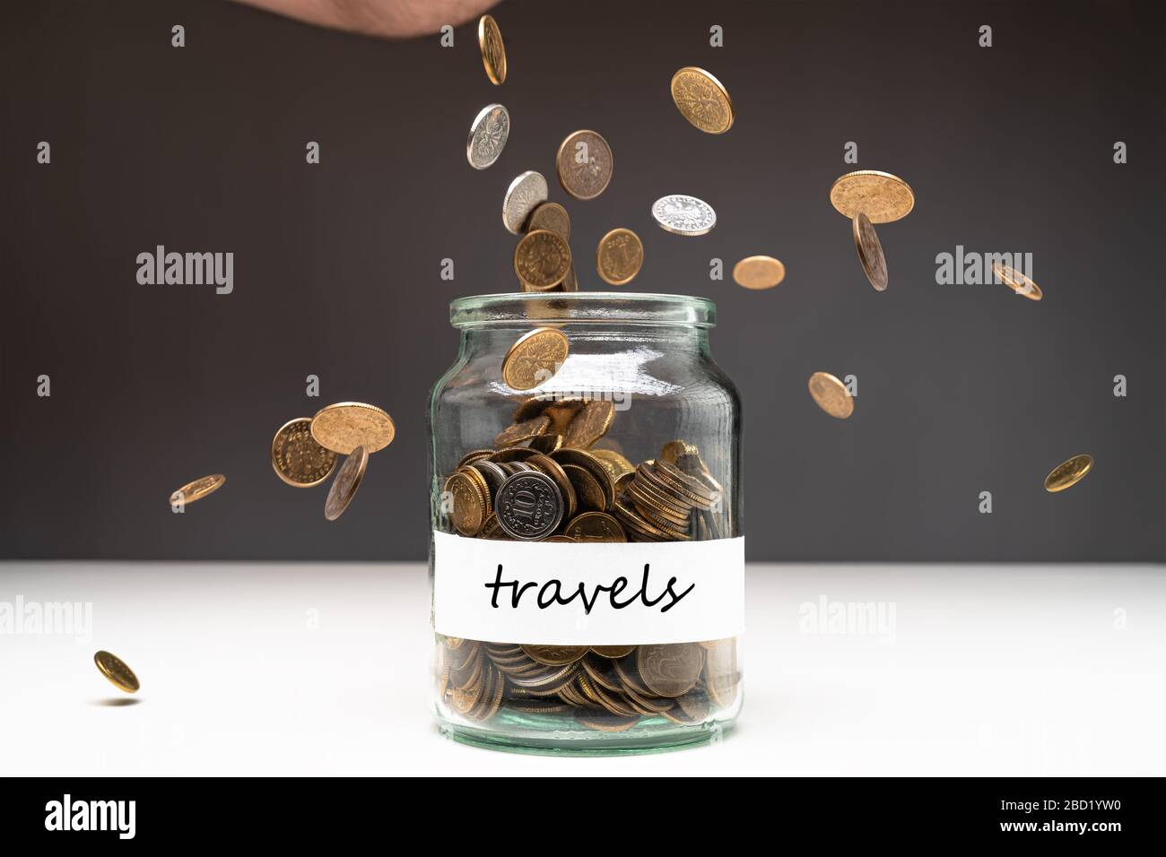 Coins in a jar with travels text on a white label. Money falling from the sky above. Savings abstract concept. Copy space. Stock Photo