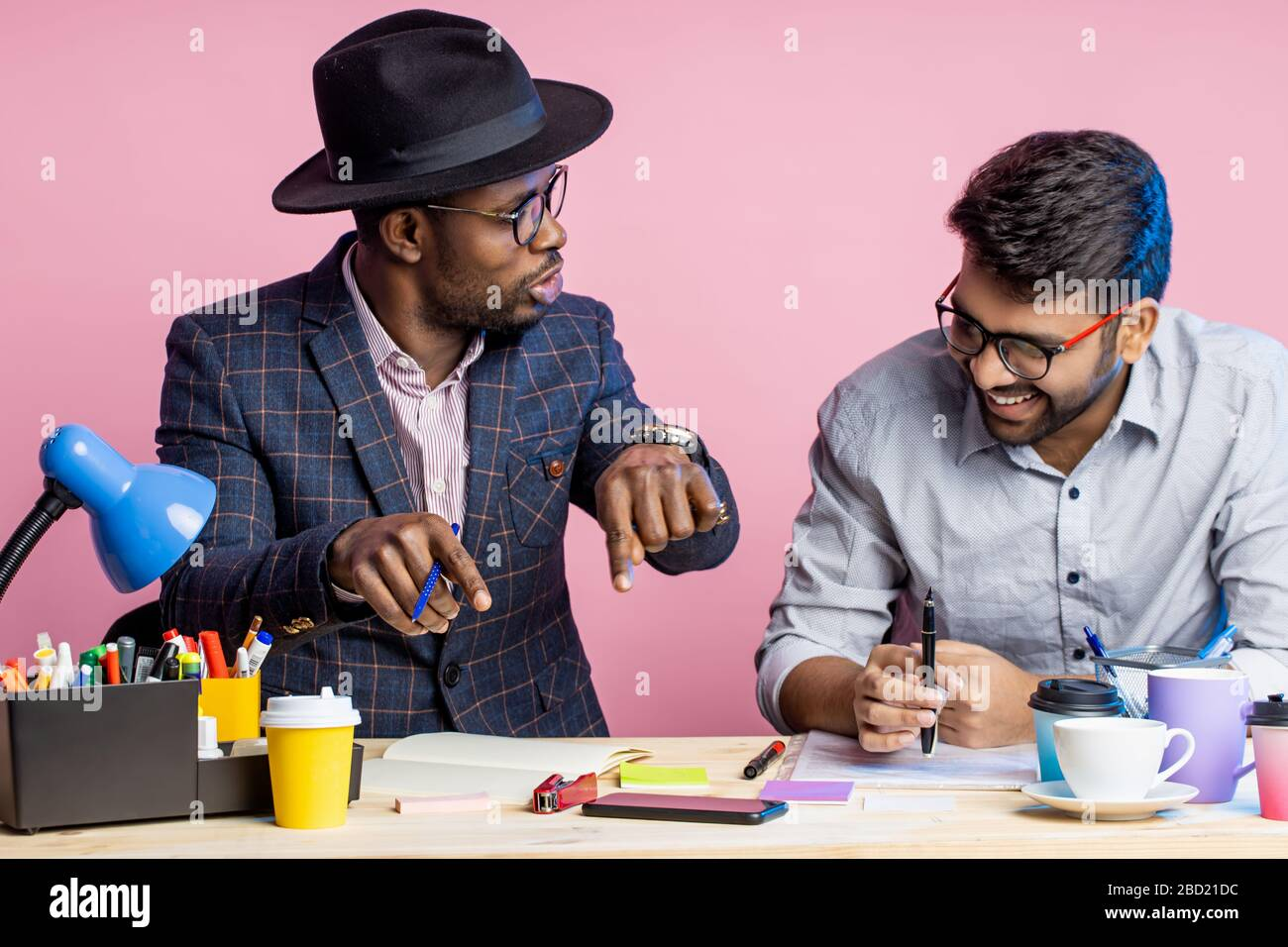 Two confident serious business people wearing suits sitting at desk in office. Dark skinned manager holding smartphone and looking at screen of gadget Stock Photo