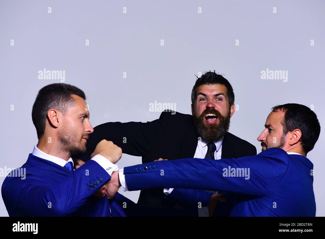 Businessmen with serious and angry faces in formal suits on grey background. Leaders fight for business leadership. Coworkers decide upon best working position. Business conflict and argument concept Stock Photo