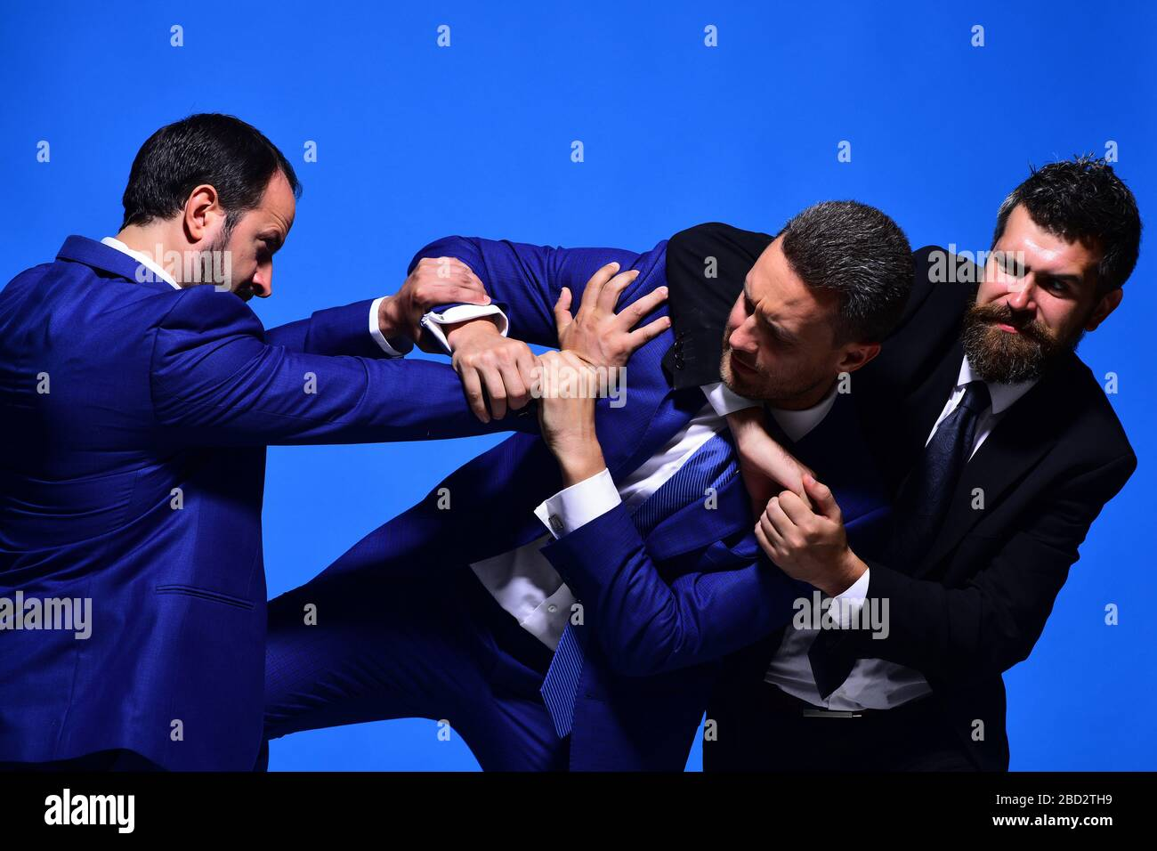 Business conflict and argument concept. Company leaders fight for business leadership. Coworkers decide upon best working position. Businessmen with strict faces in formal suits on blue background Stock Photo
