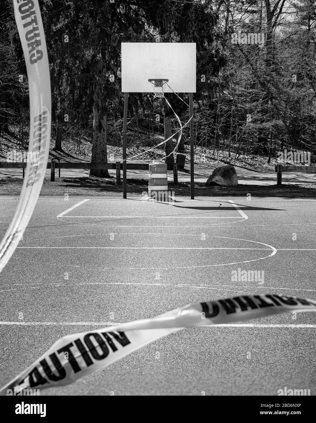 An outdoor basketball court stands closed to COVID-19 (Coronavirus). The basket is roped off by bright yellow caution tape and a pilon. From the view Stock Photo