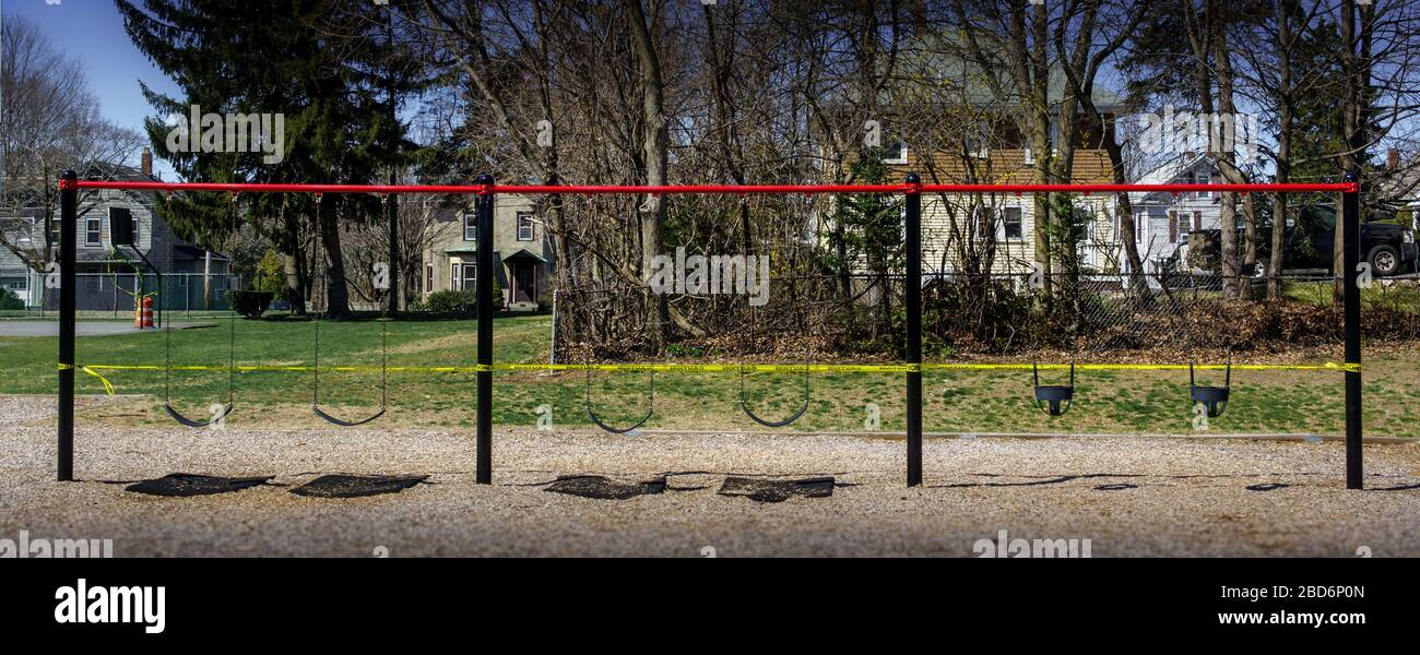 A row of children's swings is roped off with bright yellow caution tape preventing access. The entire playground has been closed due to the Corona (CO Stock Photo
