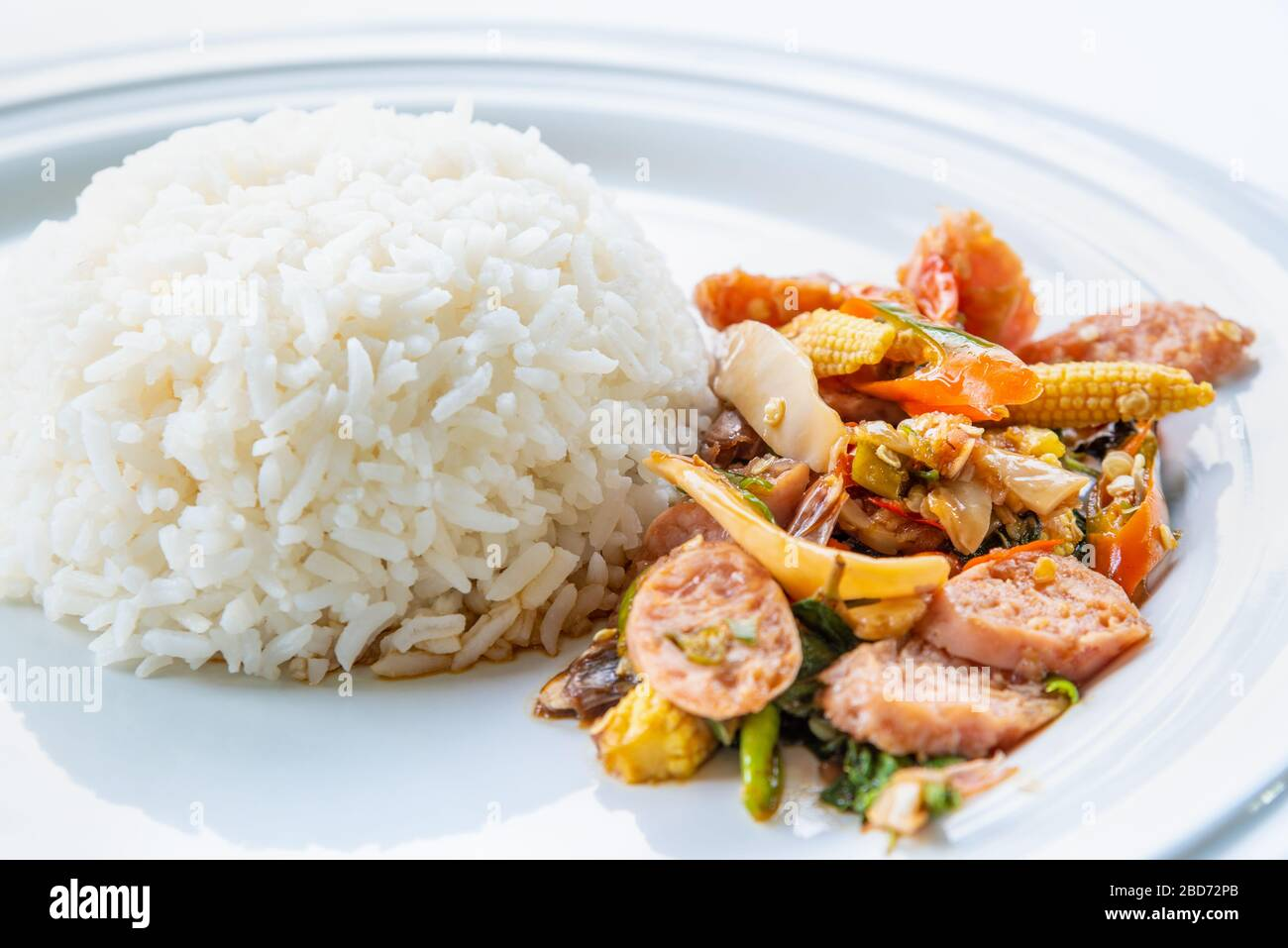 Asian spicy hot food or Thai food, closeup side view Thai sour pork or Nham fried with pepper and mixed vegetable with white cooked rice on round whit Stock Photo