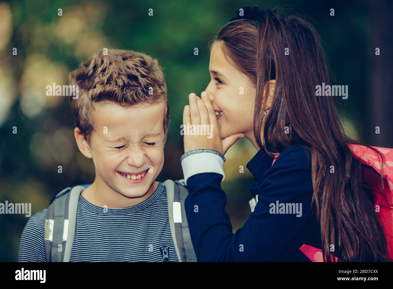 Close up two happy friends with backpacks laughing and having fun in the park. A small girl whispering something in an ear of her friend with smile an Stock Photo