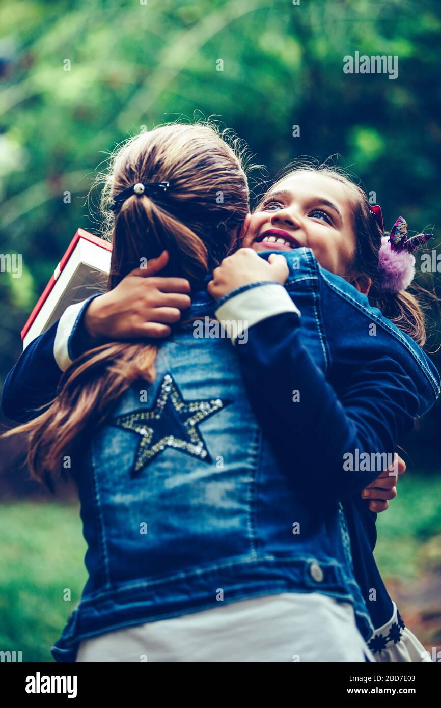 Two Best Friends Or Sisters Hugging Emotional Meeting In The Park Happy Little Girl Gives Her Smiling Friend A Gift In A Red Box Making A Surprise Stock Photo Alamy