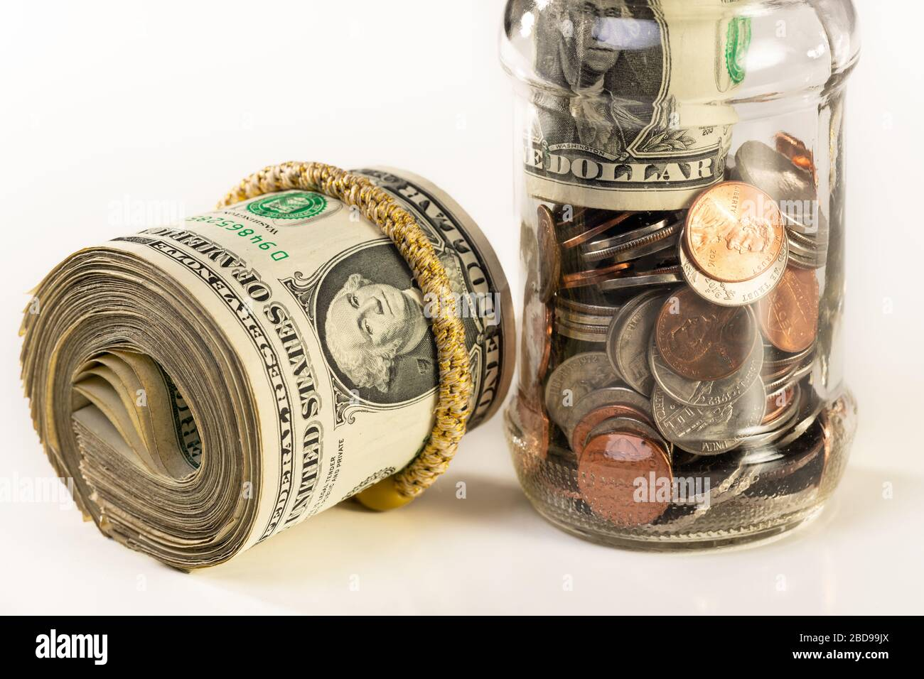 Glass jar and roll of money isolated on a white background. Stock Photo