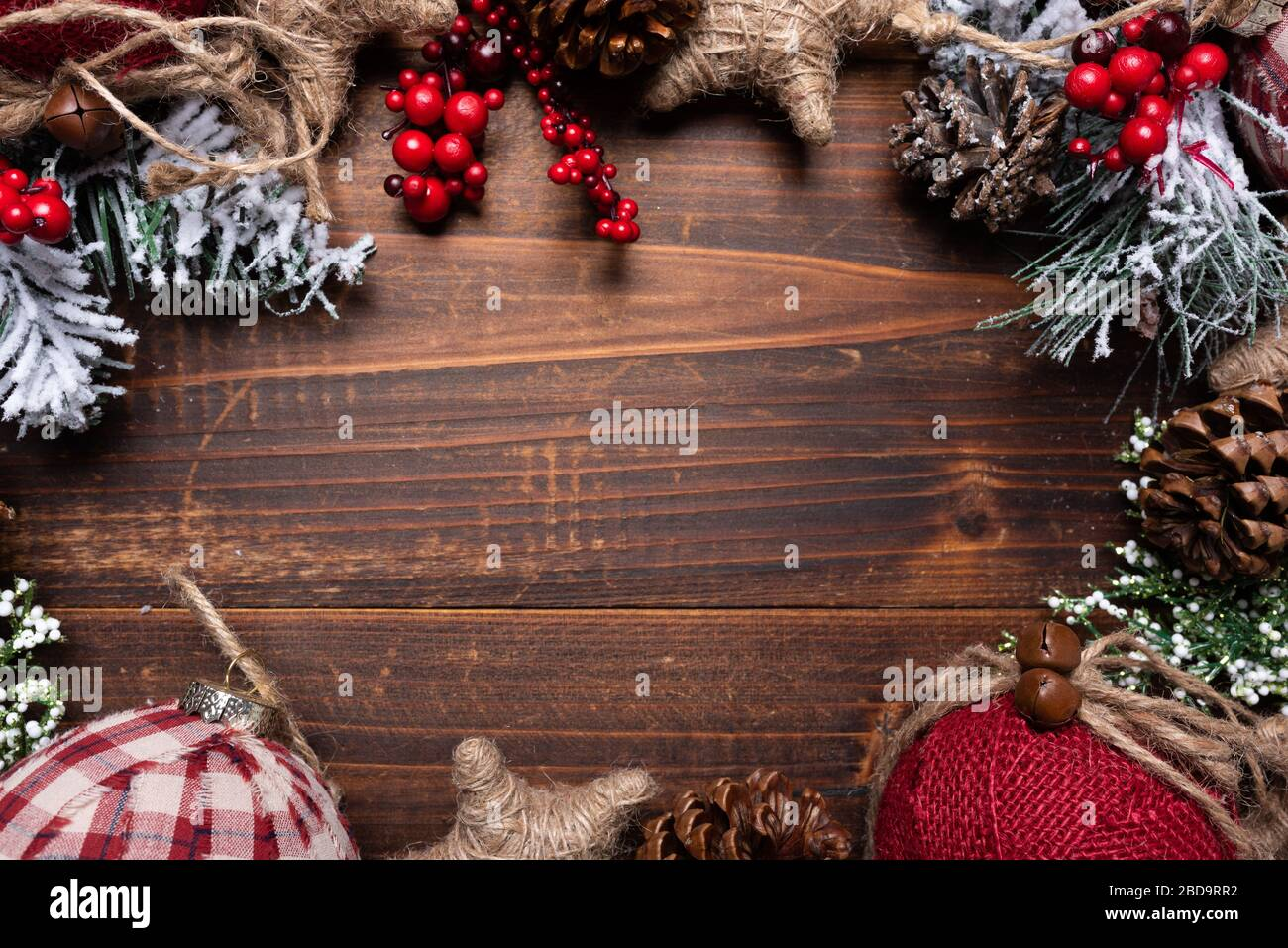 Christmas decorations on a brown wood background with copy space. Pine cones, garland, berries and pine branches Stock Photo