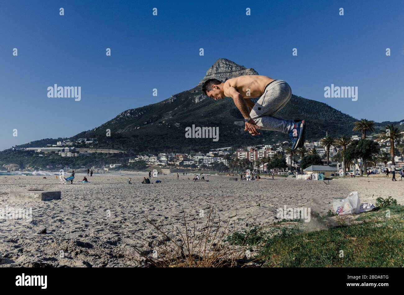 Young man on beach practicing somersaults and aerobics Camps Bay Cape Town South Africa Stock Photo