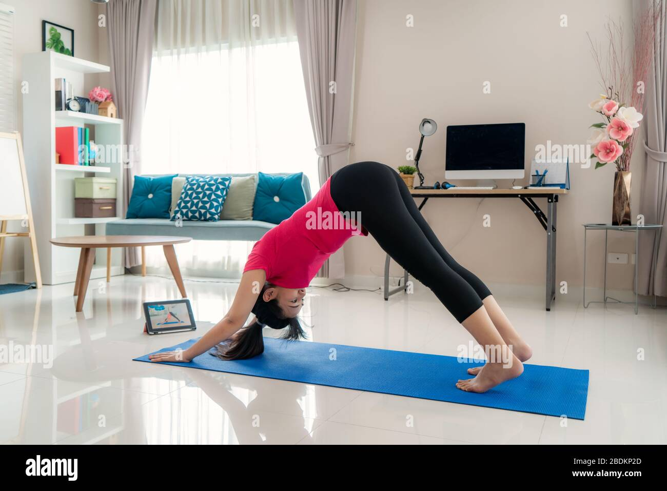 Asian woman making yoga exercise for step away from their computers to take mid-day exercise breaks via livestream videos classes on digital tablets d Stock Photo