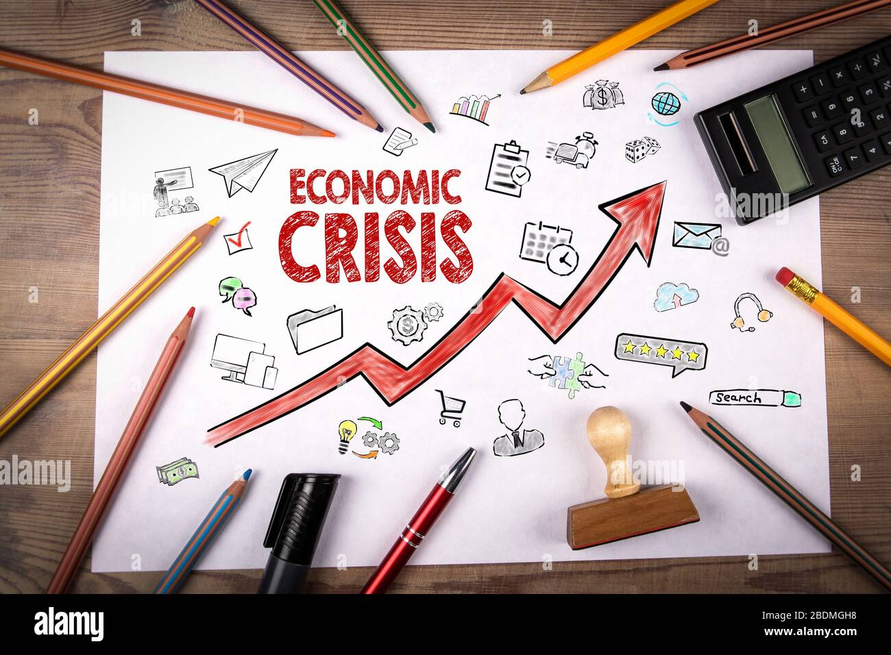 Economic Crisis. Arrow with icons. Stamp and pencil, calculator on white piece of paper Stock Photo