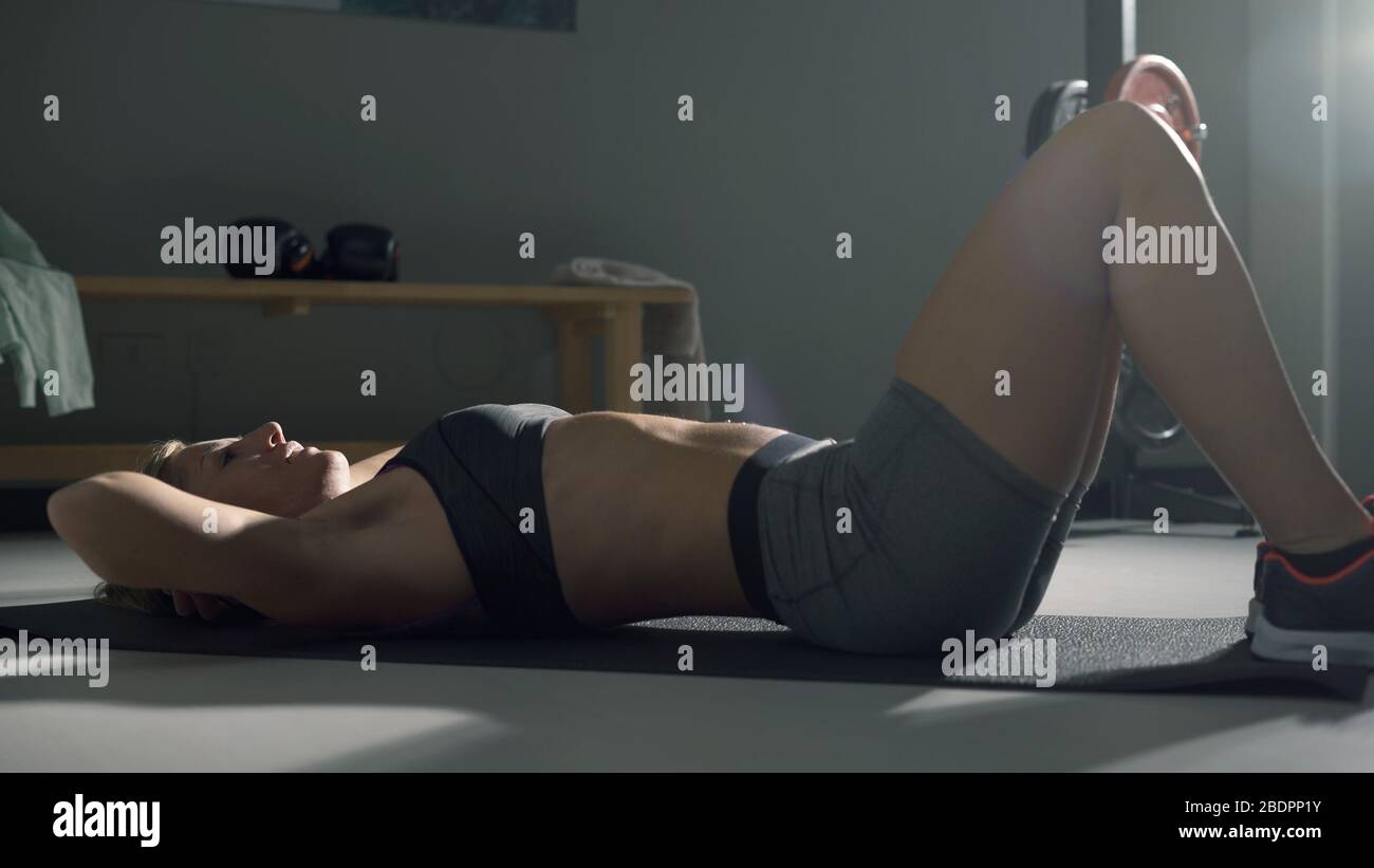 Athletic Woman Doing Abdominal Crunches On The Floor Fitness And